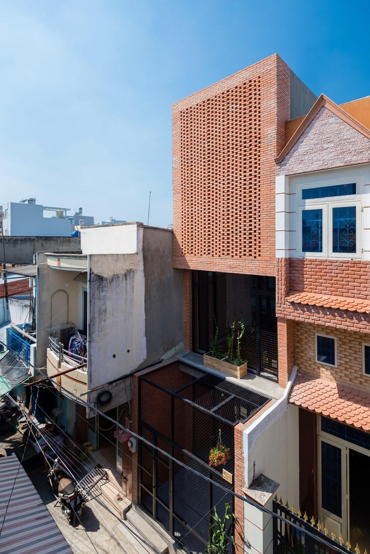 Ngôi nhà nổi bật lên giữa khu phố. Cổng và hàng rào của ngôi nhà được thiết kế đơn giản với lưới tản nhiệt kim loại để trồng những cây nho dây leo.