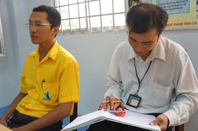 Nhân viên Tân Hiệp Phát móc bảng tên cho cán bộ ghi danh tánh
