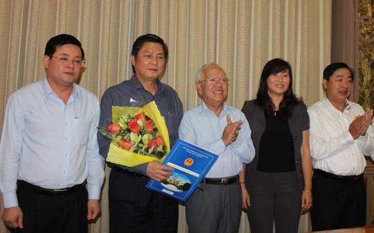 Ông Đào Anh Kiệt, Giám đốc Sở Tài nguyên Môi trường TP (cầm hoa) nhận quyết định thôi giữ chức vụ (Ảnh: Ph.Anh)