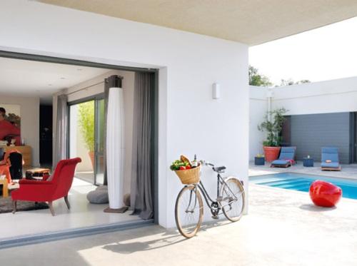 Không gian phía sau căn nhà được điểm xuyến sắc đỏ Những món đồ ấy không chỉ làm cho căn phòng sinh động hơn mà còn giúp tập trung sự chú ý đến một khu vực cần nhấn mạnh.