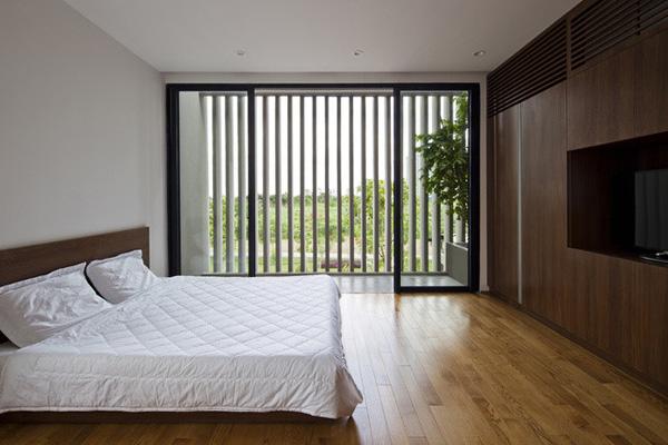 Phòng ngủ lớn thoáng đãng, qua các nan dọc có thể nhìn thấy màu xanh tươi bên ngoài.