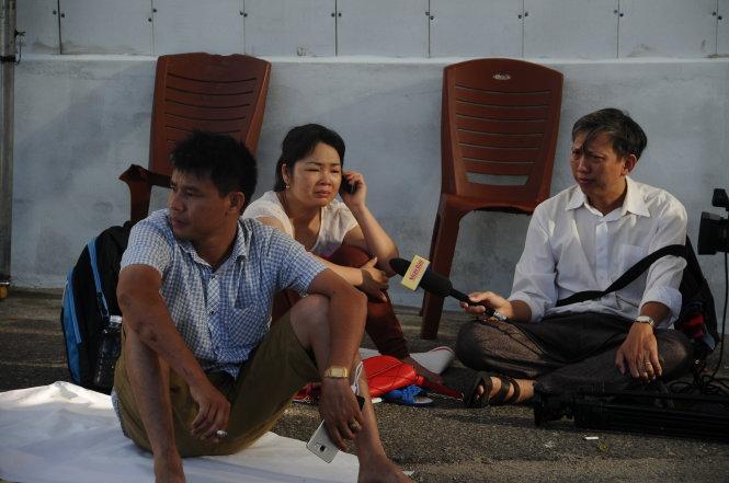 Một nhóm người thân thức trắng suốt đêm ở càng sông Hàn chờ tìn người thân từ lực lượng cứu nạn - Ảnh: ĐĂNG NAM