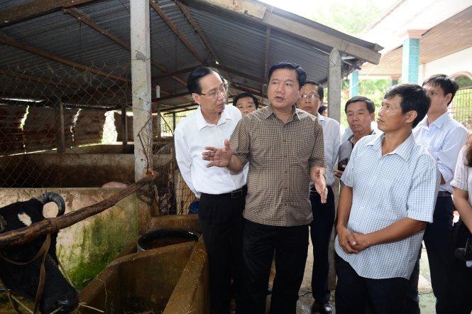 Sau cuộc làm việc, Bí thư Đinh La Thăng đến thăm gia đình anh Phan Văn Vũ, một hộ nuôi bò sữa tại ấp Thượng, xã Tân Thông Hội (Củ Chi). Ông yêu cầu phải hỗ trợ vốn và kỹ thuật để đàn bò sữa Củ Chi đạt năng suất tiệm cận tiêu chuẩn quốc tế - Ảnh: THUẬN THẮNG