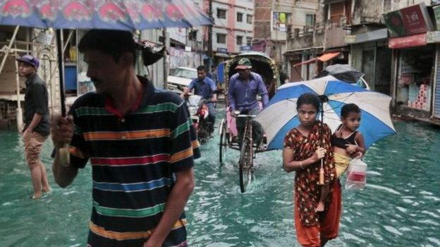 Người dân Bangladesh đi qua một con đường ngập nước do bão - Ảnh: AP