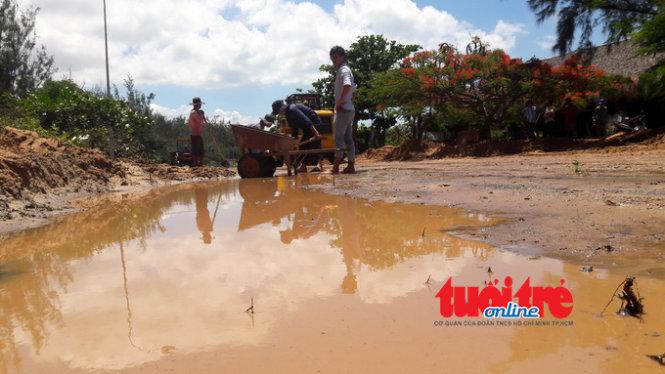 Nước bùn đỏ băng qua tuyến đường nhựa ven biển Tân Thành - Thuận Quý chạy luôn ra biển.