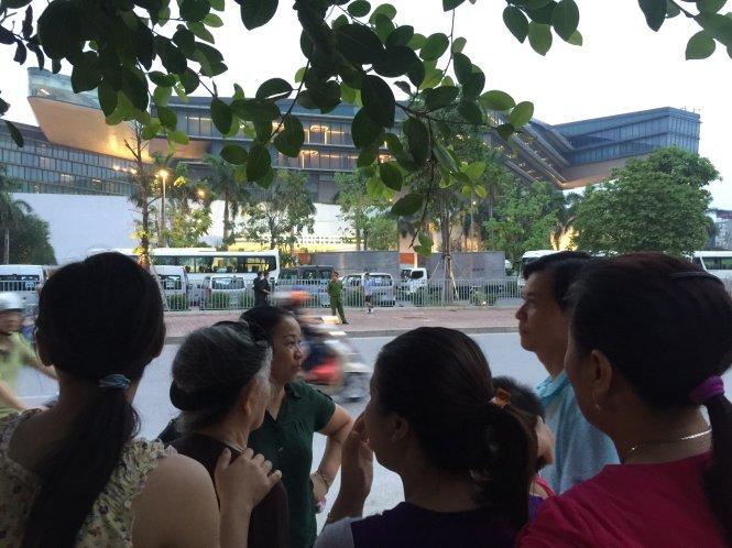 Người dân tập trung hai bên đường chuẩn bị đón tổng thống - Ảnh: Xuân Long