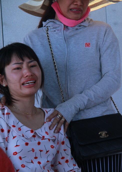 Người phụ nữ khóc ngất khi chưa tìm thấy con - Ảnh: HỮU KHÁ