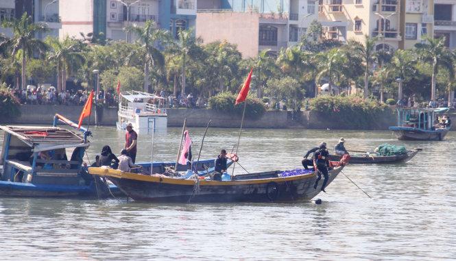 Thợ lặn trên sông tìm kiếm giữa trưa nắng - Ảnh: TRƯỜNG TRUNG