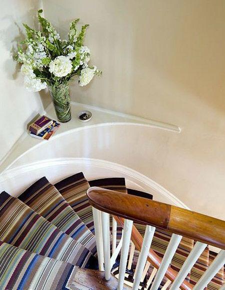 Những bậc cầu thang sẽ thêm tinh tế khi có sự xuất hiện của một lọ hoa với sắc màu tươi tắn, nhã nhặn đặt ở góc cầu thang.