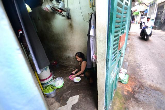 Vợ ông Trần Văn Đỏ xoay xở trong căn nhà nhỏ hình tam giác tại số 56/69 đường Thích Quảng Đức, Q.Phú Nhuận - Ảnh: Thanh Tùng