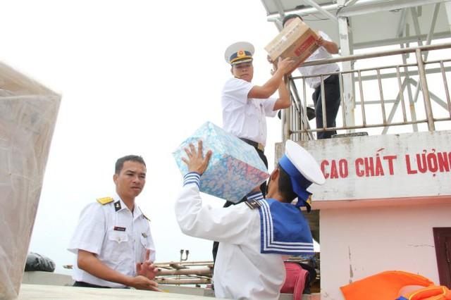 Chuyền tay chuyển quà lên đảo - Ảnh: Trần Mai.