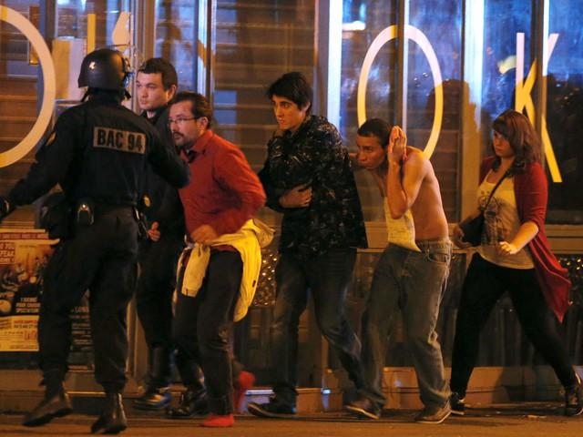 Lực lượng đặc nhiệm của Pháp đang sơ tán người dân khỏi nhà hát. Một người đàn ông bị thương đang ôm đầu.