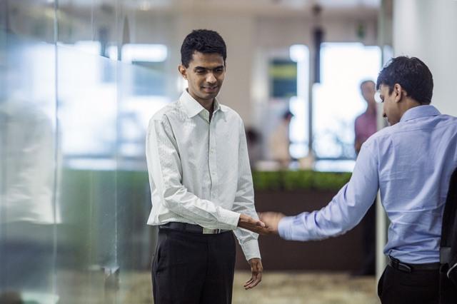 Agrawal chào hỏi đồng nghiệp tại Standard Chartered. Ảnh: Bloomberg.