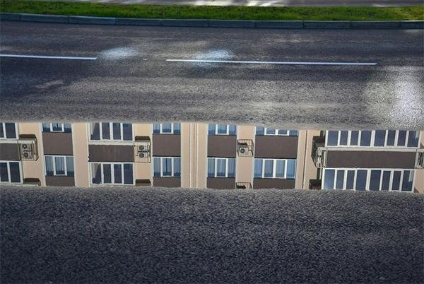 Những căn phòng vắng bóng người phản chiếu dưới một vũng nước trên đường.
